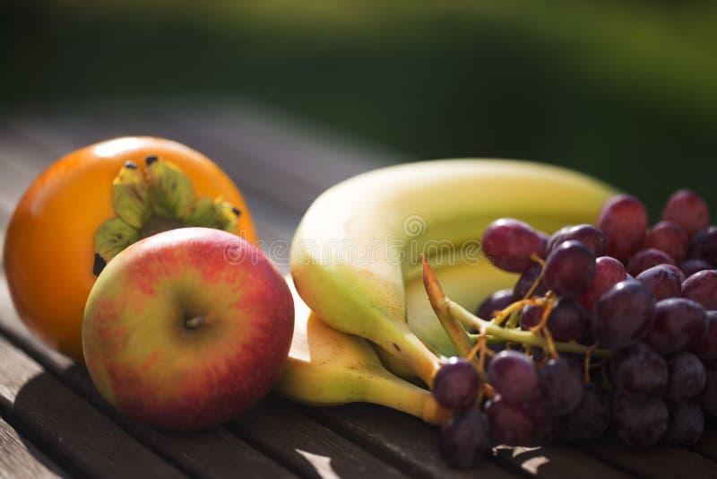äpple banane, druvor, kakier som är vetegarian arkivbild