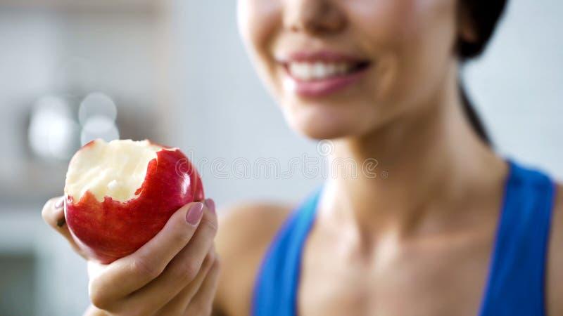 Äpple för flickainnehavtugga som fyller på hennes kropp med vitaminer, sunda tänder arkivfoton