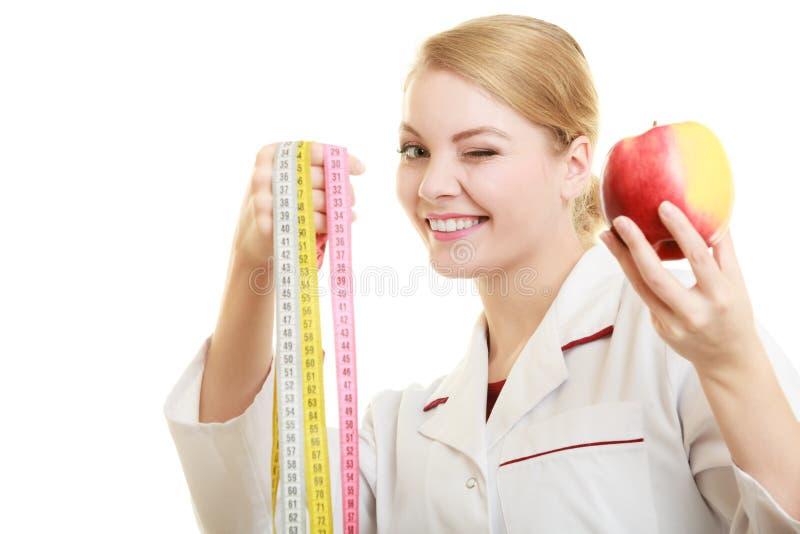 Äpple för frukt för doktorsspecialistinnehav och måttband arkivfoton