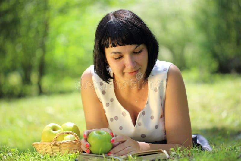 Äpple och läsebok för kvinna hållande på gräs fotografering för bildbyråer