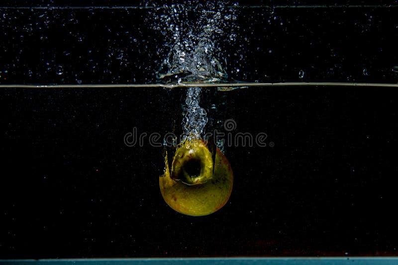 äpple som faller i mörkt vatten med färgstänk arkivfoton