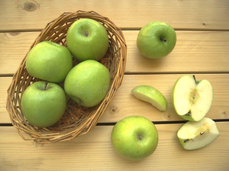 Äpplen gör grön moget och sött i en korg och klipper in i stycken royaltyfri foto
