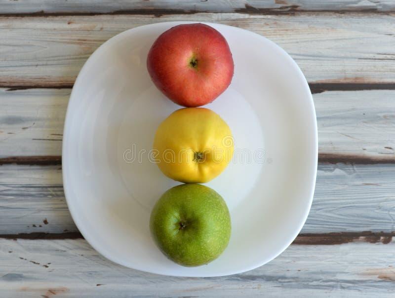 Äpplen i en platta på tabellen fotografering för bildbyråer