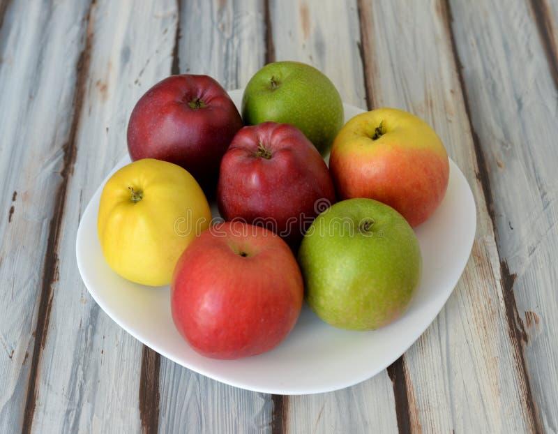 Äpplen i en platta på tabellen arkivfoton