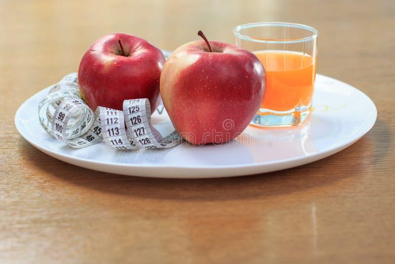 Äpplen, linjal på plattan och multivitaminfruktsaft i exponeringsglas arkivbild
