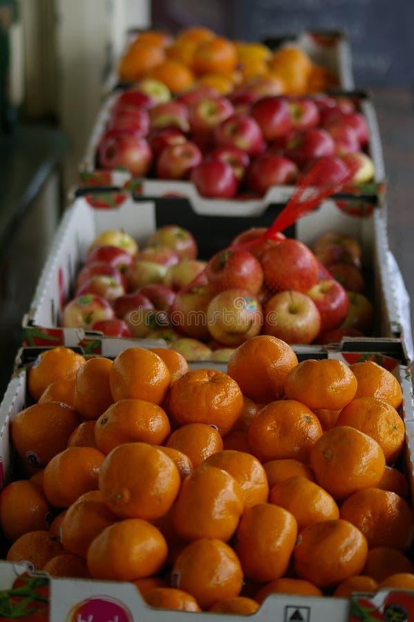 Äpplen och apelsiner som säljs på en lokal grön specerihandlare arkivfoton