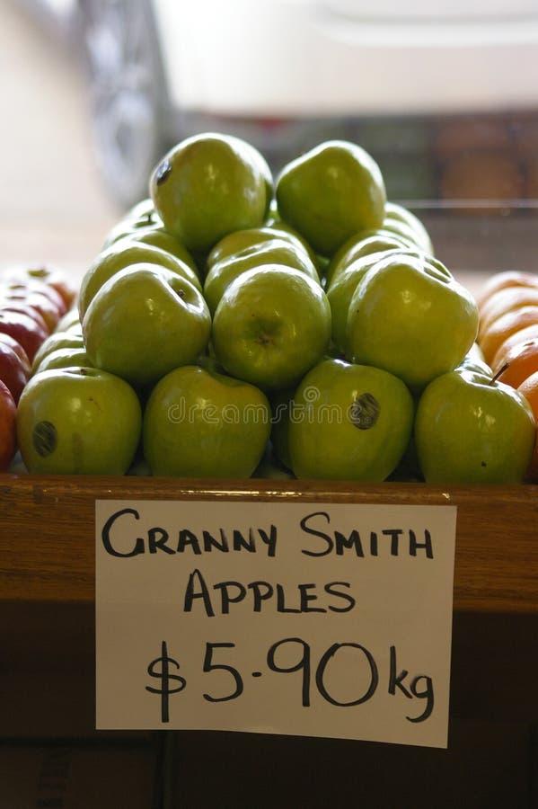 Äpplen och apelsiner som säljs på en lokal grön specerihandlare royaltyfria foton