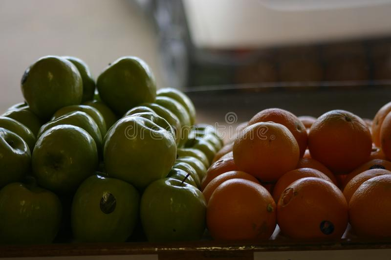 Äpplen och apelsiner som säljs på en lokal grön specerihandlare royaltyfria bilder