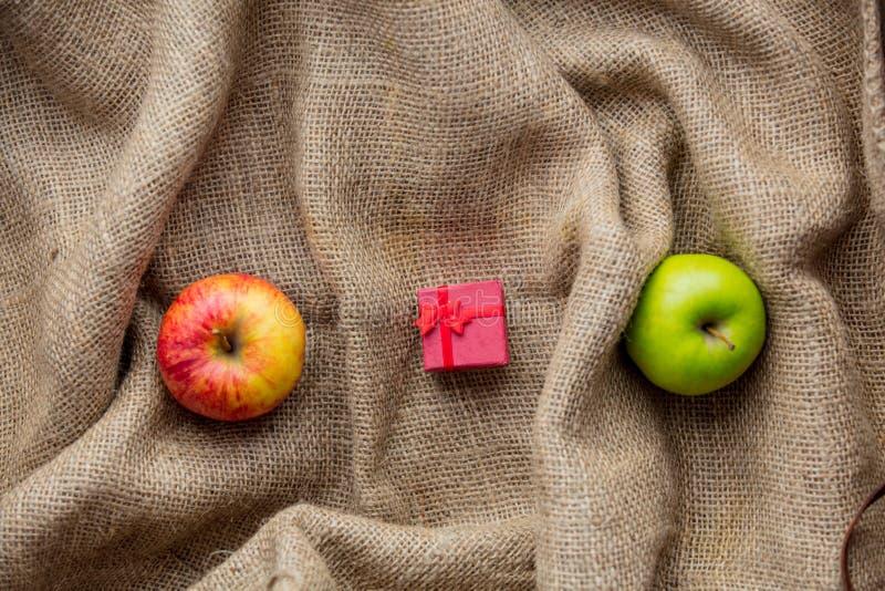 Äpplen och liten gåvaask arkivfoto