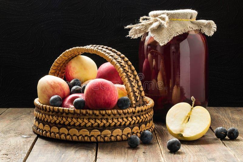 Äpplen och slån i en korg och på burk fruktkompott av a fotografering för bildbyråer