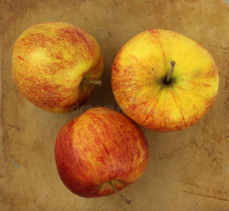 Äpplen på en gammal lantlig stenskärbräda arkivfoton