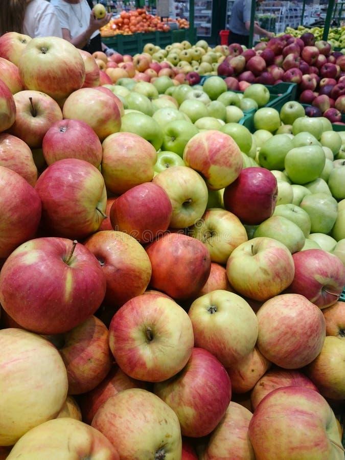 Äpplen på räknaren i supermarket I bakgrunden väljer köpare frukt royaltyfria foton