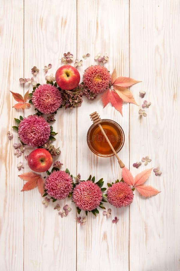 Äpplen, rosa färgblommor och honung med kopieringsutrymmeformen en blom- de arkivfoto