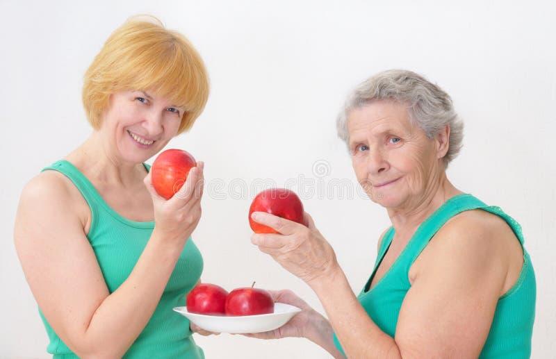 äpplen som äter två kvinnor royaltyfri foto