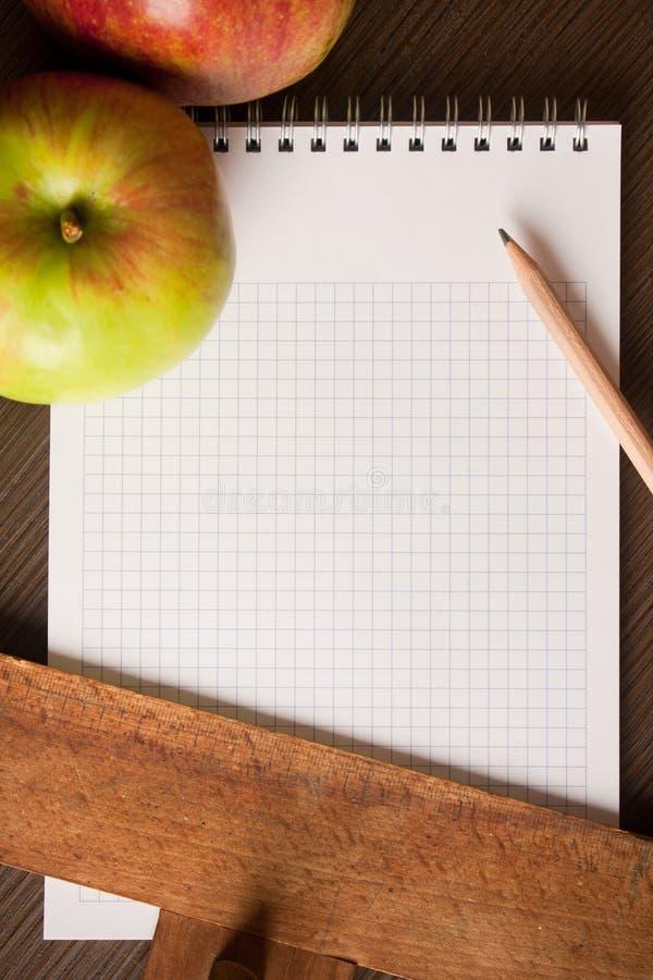 äpplen tömmer läroboken fotografering för bildbyråer