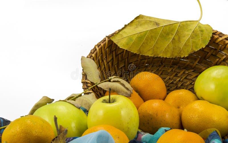 Äpplen, tangerin och en vide- korg på en vit bakgrund royaltyfria bilder