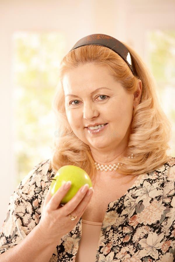 äpplepensionärkvinna arkivfoto