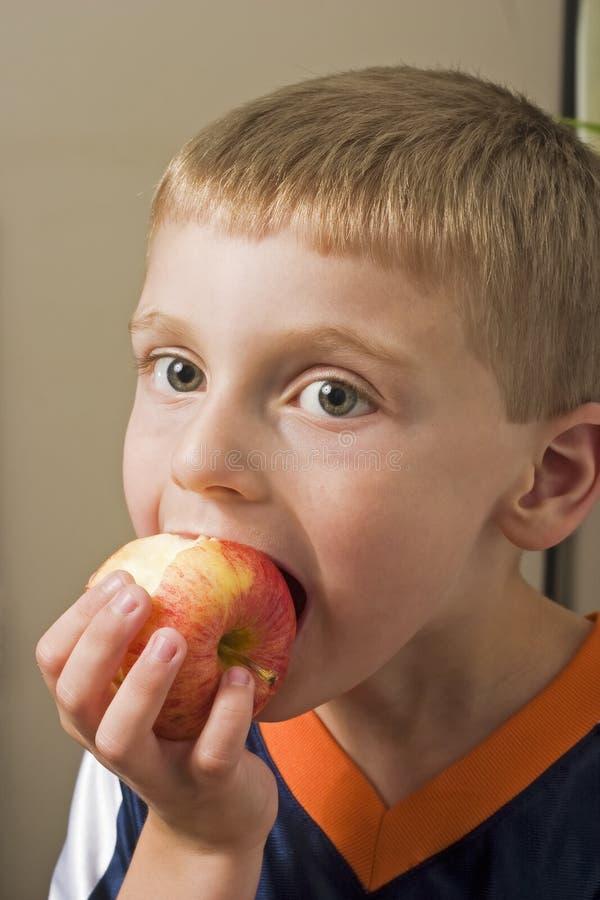 äpplepojke som äter barn royaltyfri foto