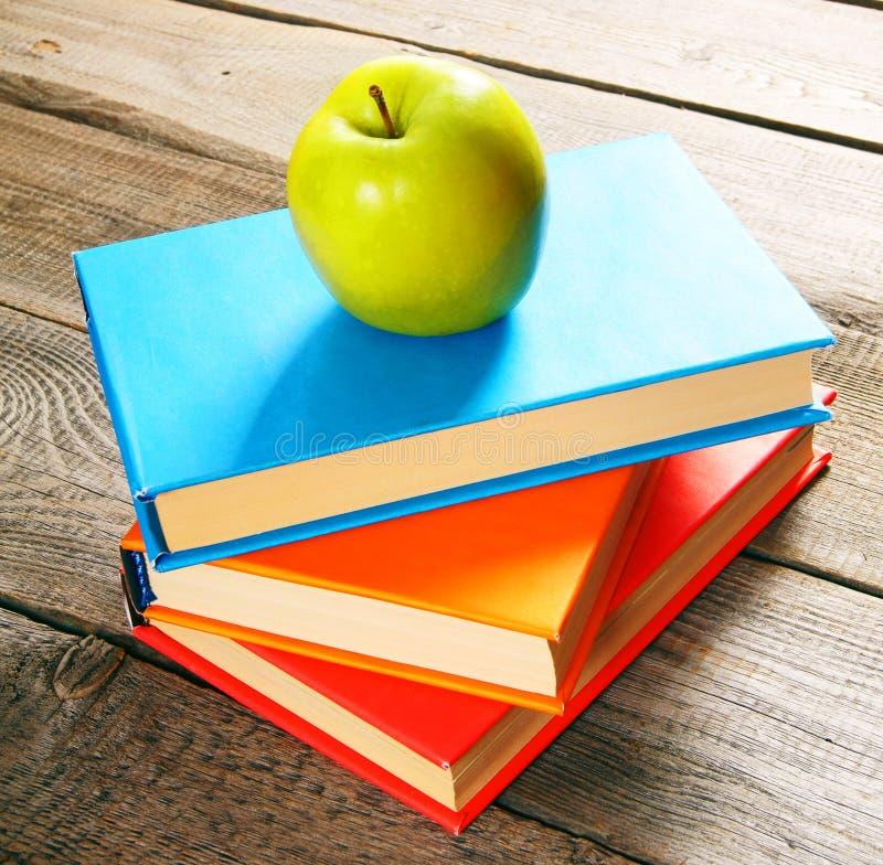äpplet books green På träbakgrund royaltyfria bilder