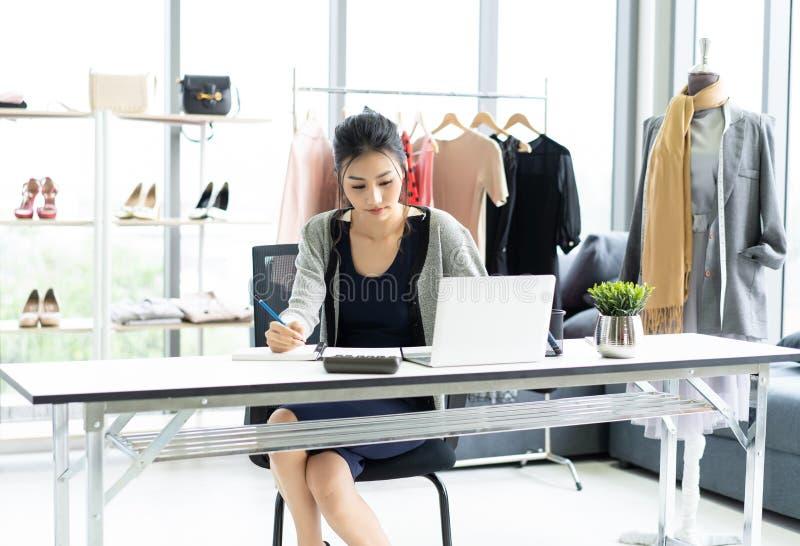 Är den asiatiska kvinnan för den unga affären som sitter på tabellen och tar anmärkningar i anteckningsbok på tabellen, bärbara d royaltyfria bilder