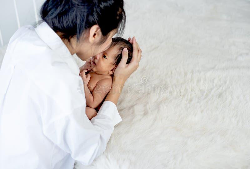 Är den asiatiska modern för den vita skjortan kyssa, och rymma nyfött behandla som ett barn nära fluffig säng med begreppsförälsk royaltyfri fotografi