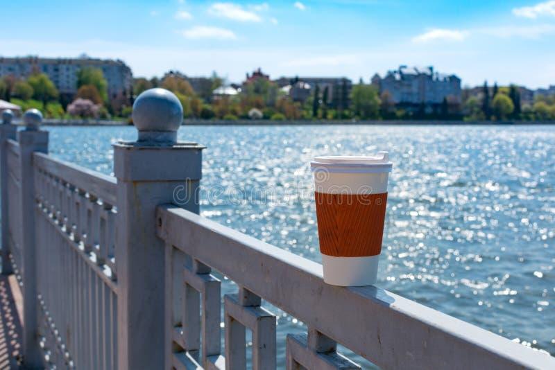 Är den enkla koppen för kaffe på staketThe sjön och staden i bokeh på bakgrunden arkivfoton
