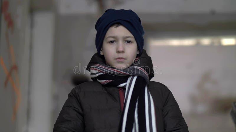Är den ensamma ledsna pojken för ståenden i ett förfallet hus i vinter royaltyfri foto