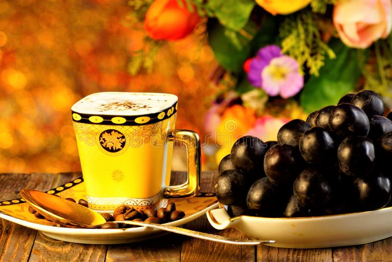Är den förnyande drinken för kaffe och druvorna en läcker läckerhet på bakgrunden av sommarträdgårdblommor och ferieljus royaltyfri fotografi