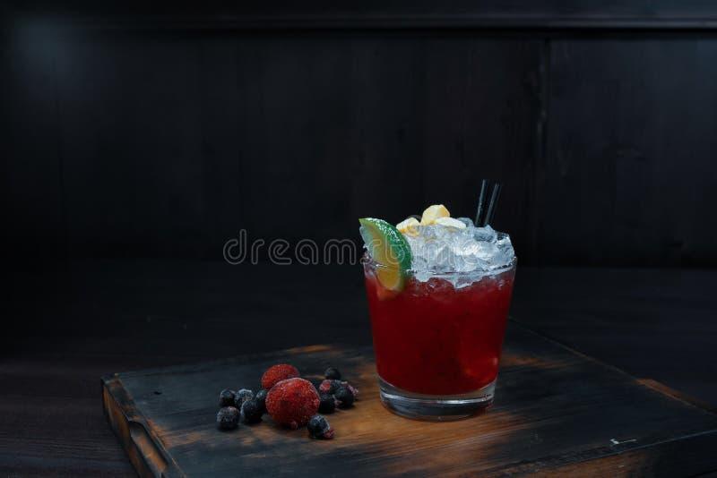 Är den söta alkoholiserade röda coctailen för frukt med is med bärsirap och vodka i ett kristallexponeringsglas på tabellen i stå royaltyfri fotografi