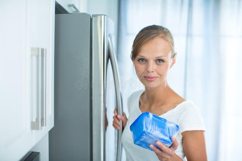 Är detta fortfarande fint? Nätt ung kvinna i hennes kök arkivbild
