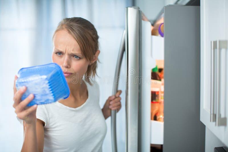 Är detta fortfarande fint? Nätt ung kvinna i hennes kök vid fren arkivbild