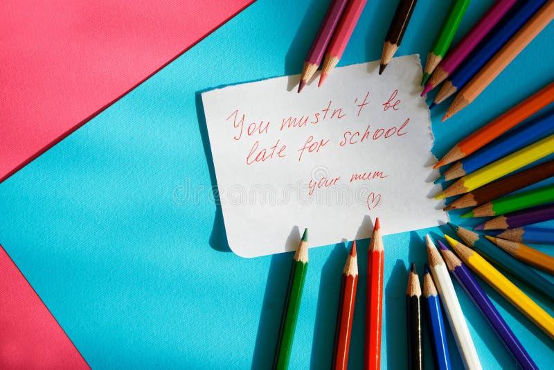 """""""är du mustn` t sen för school"""", - anmärkningen för en skolpojke från älska lögner för en moder bredvid de kulöra blyertspenno royaltyfri foto"""