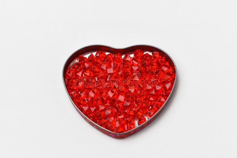 Är grå bakgrund för valentindagen på den en ask i form av en hjärta, det exponeringsglaskristaller av rött, scharlakansrött, rubi royaltyfria bilder