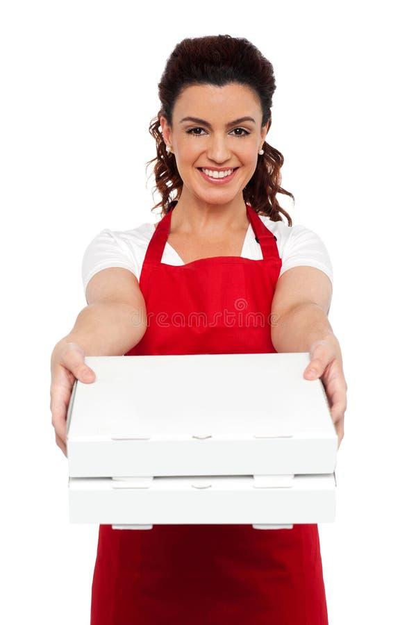 Är här din beställningsherrn. Varm pizza på din tröskel royaltyfri bild
