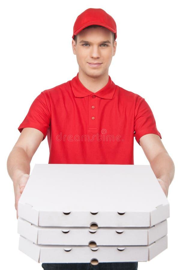 Är här din pizza! Gladlynt ungt bud som ut sträcker a arkivbild