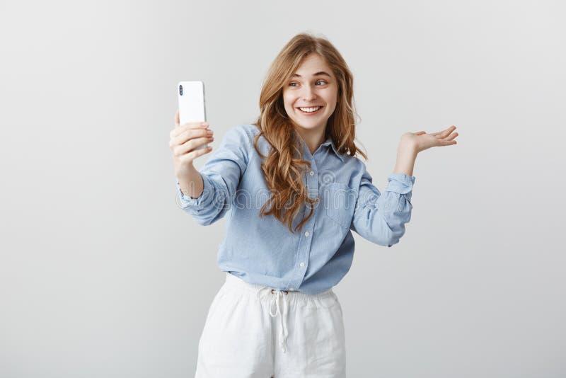Är här mitt rum Stående av den upphetsade lyckliga snygga kvinnan i blå blusvisning omkring medan video som pratar via arkivbild