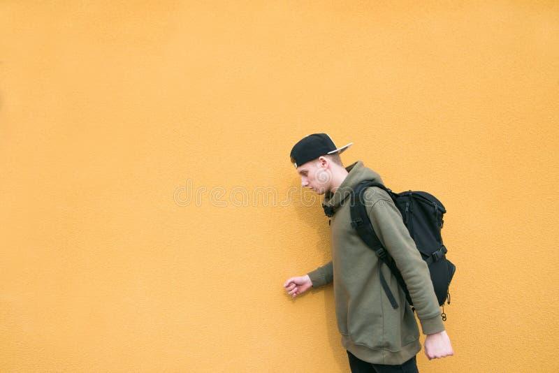 Är iklädda tillfälliga kläder för den unga mannen och en ryggsäck på hans baksida på bakgrunden av en orange vägg arkivfoto