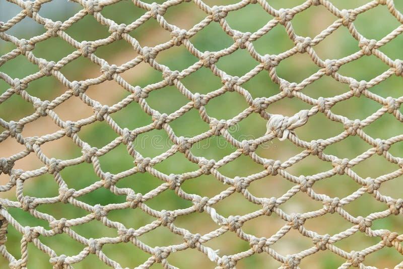 Är netto textur för det vita tappningrepet på bakgrund för grönt gräs arkivbilder