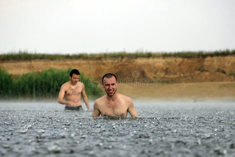 Är ung man två i en flod under regnet royaltyfria bilder