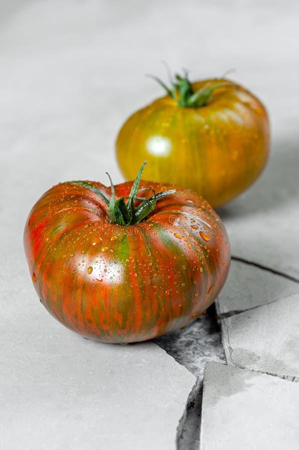Ärftliga tomater Två tomater av olika färger på en grå konkret tabell med en spricka arkivbild