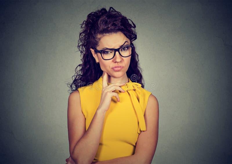 Ärgerliche verärgerte mürrische junge pessimistische Frau mit schlechter Haltung denkend, Sie betrachtend stockfoto