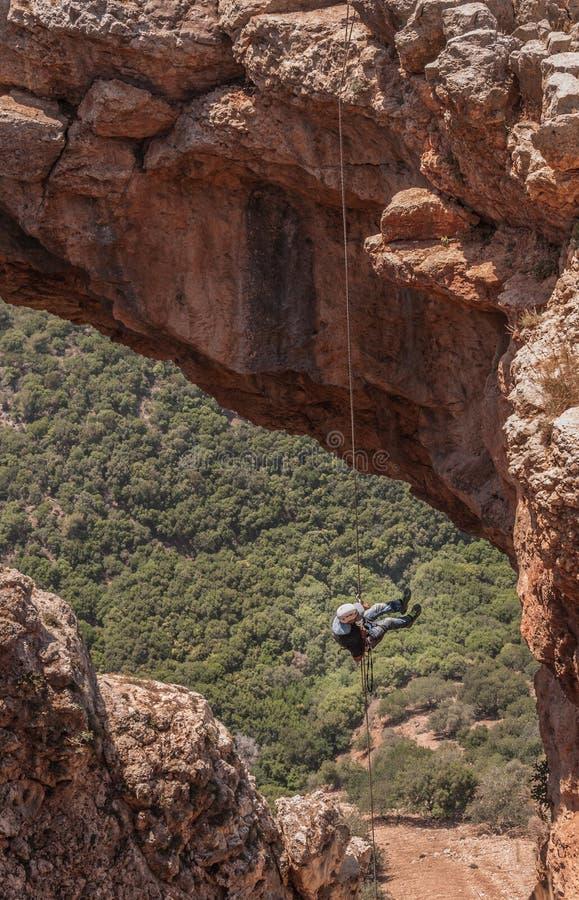 Ärke- grotta som Rappelling - inställd i luften arkivfoto