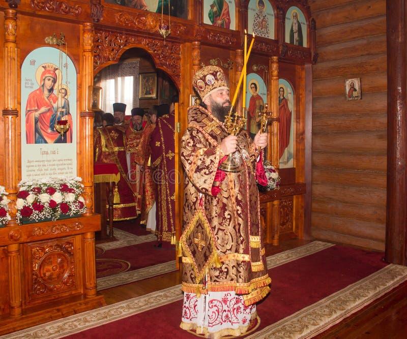 Ärkebiskopen med bränningvaxstearinljus på den gudomliga liturgin i den ortodoxa kyrkan arkivfoto