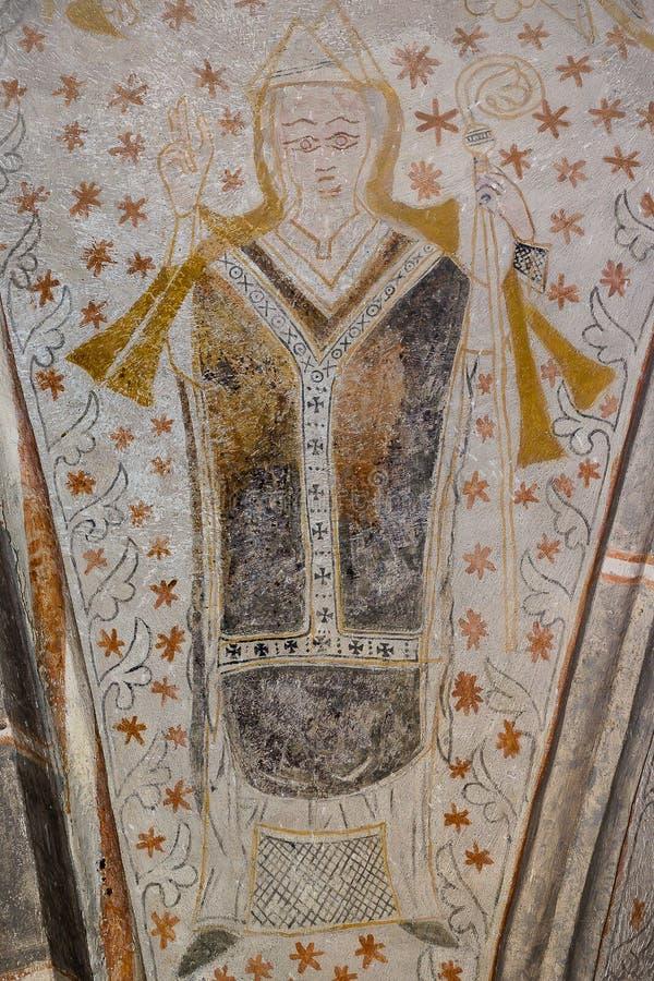 Ärkebiskopen rymmer en skurk i hans vänstersidahand och välsignar med hans r royaltyfri foto
