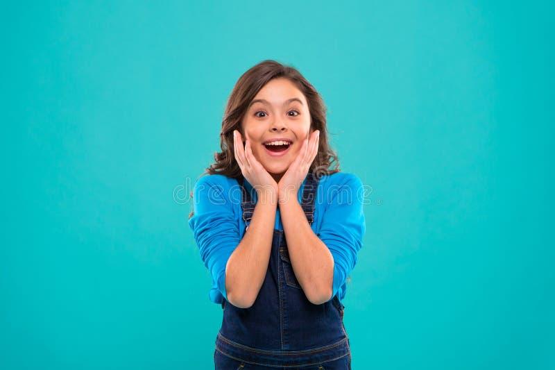 Ärlig spänning Långt sunt skinande hår för ungeflicka att bära tillfällig kläder Upphetsad lycklig framsida för liten flicka Lyck arkivbild