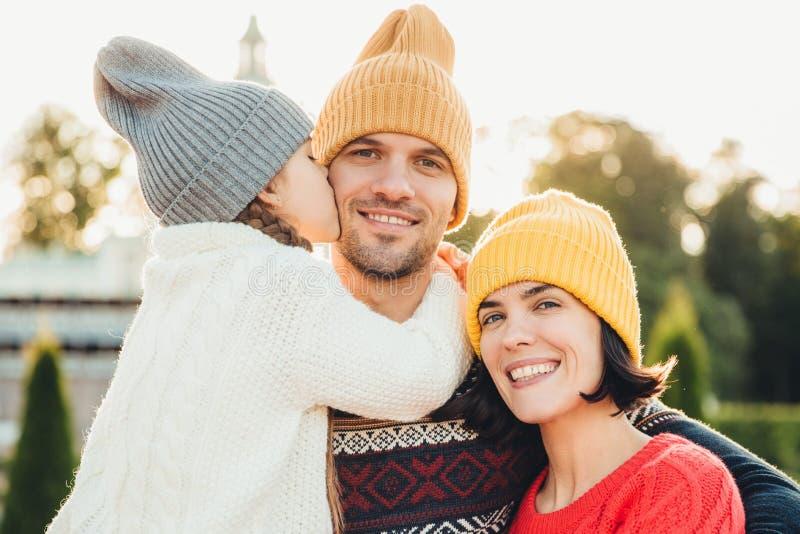 Ärliga sinnesrörelser Den lilla gulliga flickan i stucken hatt och den vita varma tröjan kysser hennes fader med förälskelse Vänl royaltyfria foton