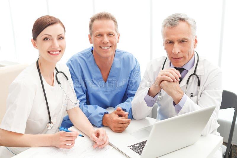Ärzteteam bei der Arbeit. Nettes Ärzteteam, das zusammen an sitzt lizenzfreie stockbilder