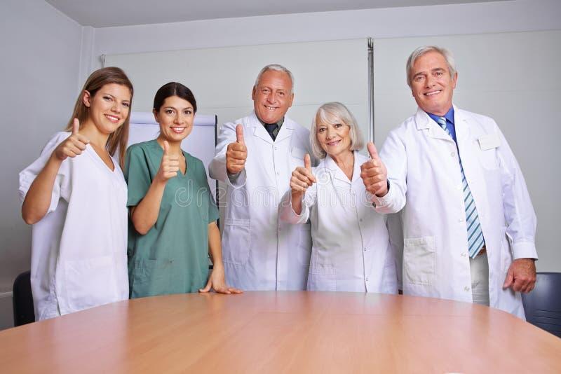 Ärzteteam, das Daumen hochhält lizenzfreie stockbilder