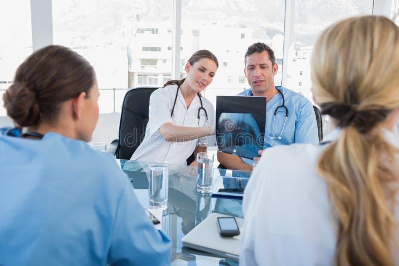 Ärzteteam, das einen Röntgenstrahl analysiert lizenzfreie stockfotos