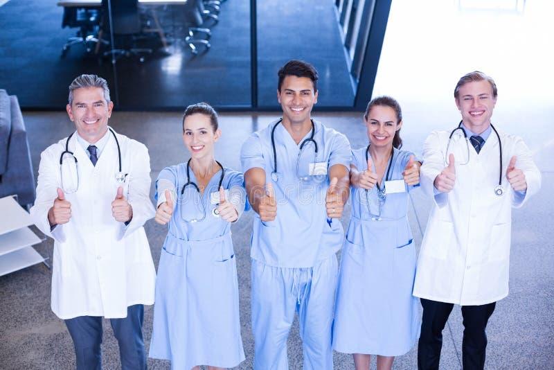 Ärzteteam, das ihre Daumen und das Lächeln darlegt stockfotografie